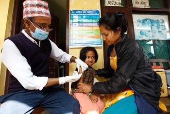 Un travailleur de santé vaccine un enfant de quatre ans contre la rougeole dans le village de Bungamati, au Népal. Photo UNICEF/Panday