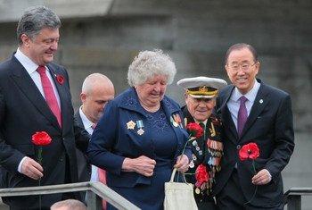 Le Secrétaire général, Ban Ki-moon (à droite), avec le Président ukrainien Petro Porochenko, et un vétéran de la Seconde Guerre mondiale de 96 ans et ancien prisonnier du camp d'Auschwitz, Ivan Zaluzhnyi (2ème à droite). Photo : ONU