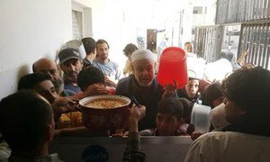 Civilians displaced from Yarmouk wait to receive a hot meal in a collective shelter in Yalda, Syria.