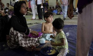 A rescued boat woman and her two children eat some welcome food at a centre in Kuala Cangkoi, Indonesia.
