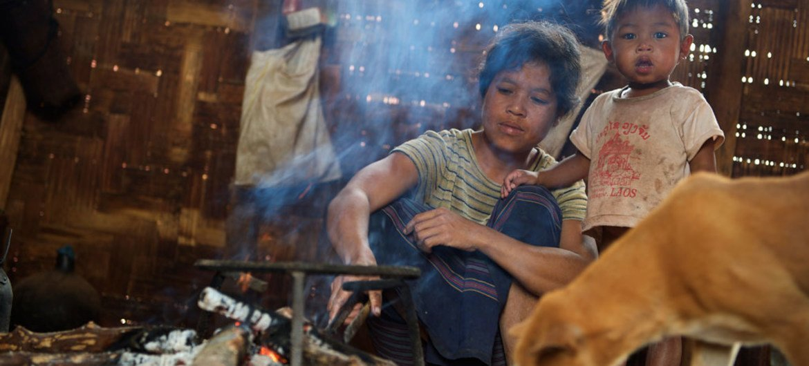 A woman lights a fire at her home in Laos. UNICEF/LAO-2015-Noorani-0083/Noorani