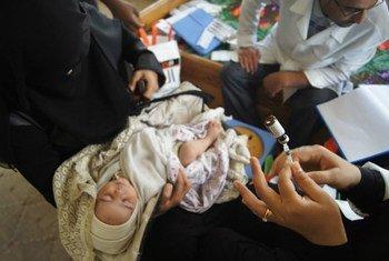Une mère déplacée à Sanaa, au Yémen, fait vacciner son nouveau-né. Photo OMS Yémen