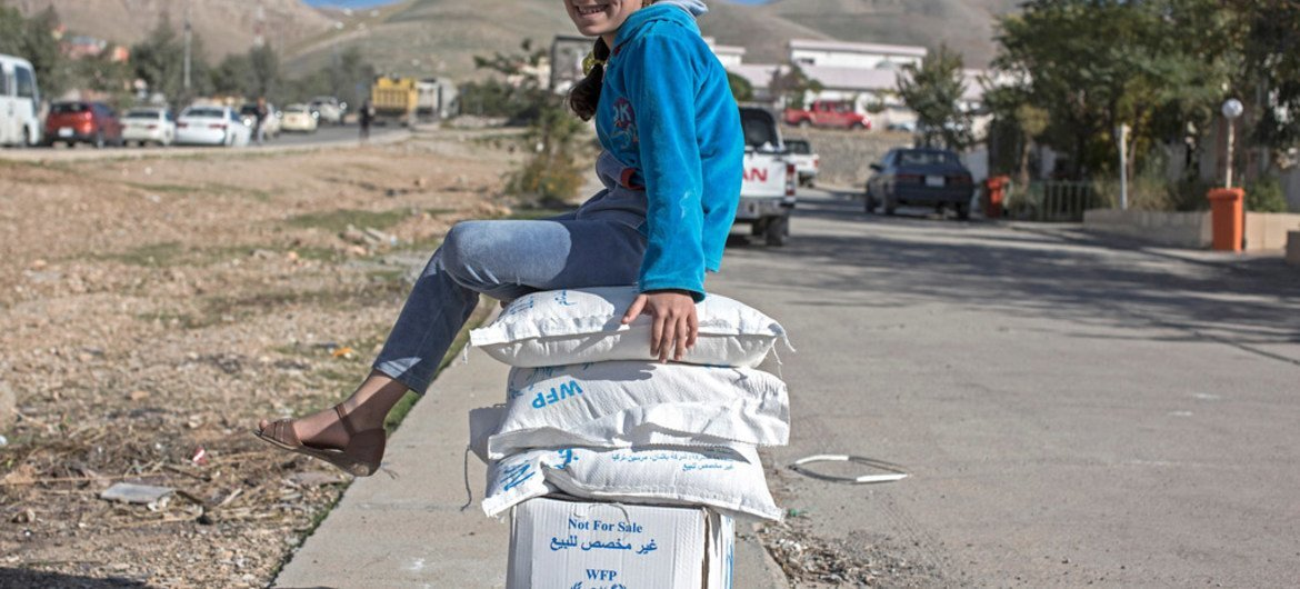 Seven-year-old Safa guards her family's World Food Programme boxes by sitting on top of them, in Sulaymaniyah, Iraq.