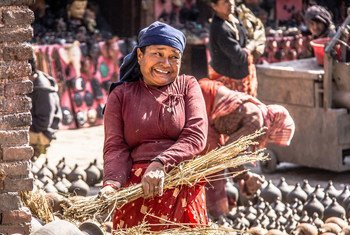 A woman in front of traditional pottery in Kathmandu's Durbar Square.