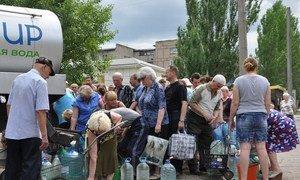 En Ukraine, des habitants de Stakhanov, dans la région de Louhansk, collectent de l'eau potable (juin 2015). Photo UNICEF Ukraine