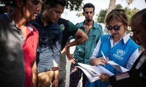 UNHCR staffer helps refugees and migrants to register at the local police station on Kos Island in Greece.