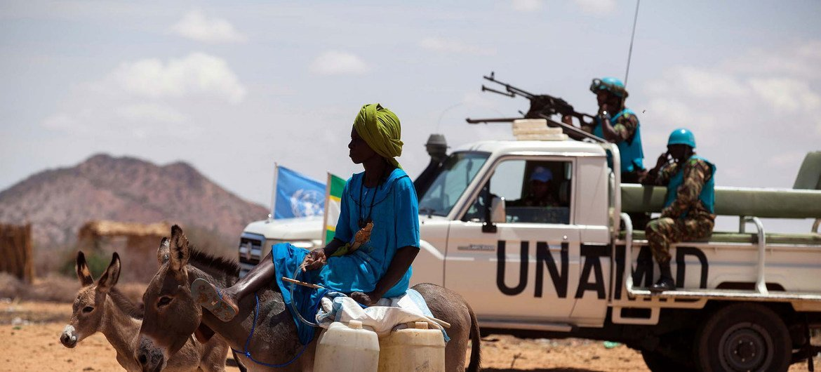 A woman rides a donkey loaded with water jerry cans, while UNAMID troops from Tanzania conduct a routine patrol in the camp for internally displaced persons (IDP) in Khor Abeche, South Darfur.