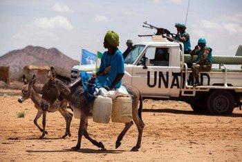 Une femme sur son âne alors que des Casques bleus de la MINUAD mènent une patrouille dans un camp de déplacés à Khor Abeche, au Sud-Darfour. Photo MINUAD/Albert González Farran