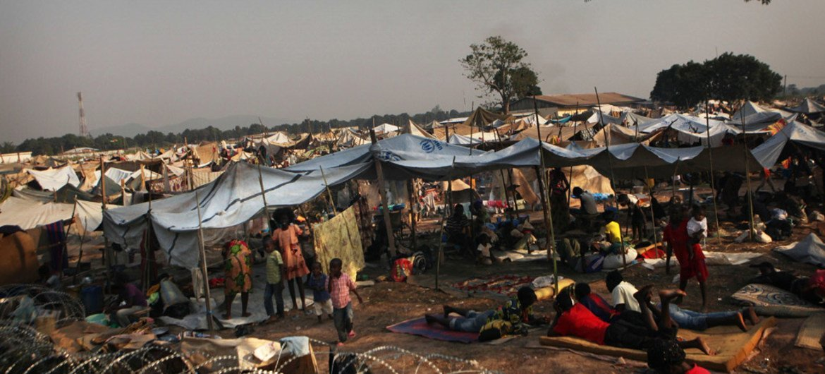 Displaced children and adults shelter outside a barbed-wire fence, in a camp set up behind Mpoko International Airport in Bangui, Central African Republic (CAR).