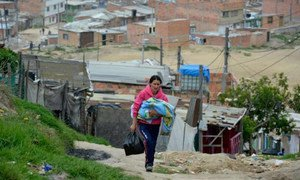A mother carries her baby through the winding, steep streets of the settlement of Altos de la Florida, Soacha, Colombia. The majority of people in the settlement have been displaced from other areas of Colombia because of fighting and threats by various armed factions.