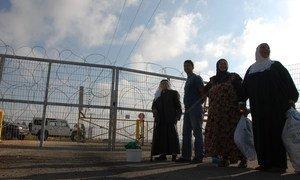 Des Palestiniens en Cisjordanie à côté d'un checkpoint