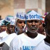 """Singers wearing hats advocating """"No Torture"""" line up before performing at a Human Rights Day event outside of Mogadishu Central Prison in Somalia."""