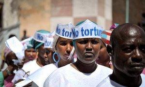 """2013年12月10日,索马里摩加迪沙中央监狱外举行""""世界人权日""""纪念活动,头戴写有""""无酷刑""""字样帽子的歌手们正在准备表演。"""