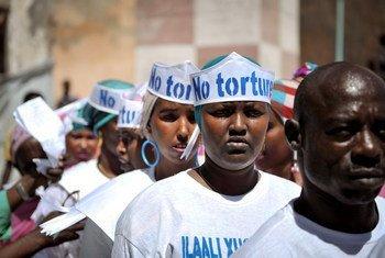"""在2013年12月10日于索马里摩加迪沙中央监狱外举行的世界人权日纪念活动中,头戴着""""无酷刑""""字样帽子的歌手们正在准备表演。"""