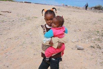 طفلة من المشردين داخليا تحمل شقيقتها في الأكاديمية البحرية بالقرب من طرابلس.