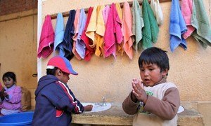 Two small children wash their hands with soap at a hand-washing station at the Sayariy Warmi early childhood development (ECD) centre in Sucre, Bolivia.