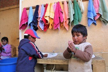 Dos niños en Bolivia se lavan las manos en una estación apoyada por UNICEF.