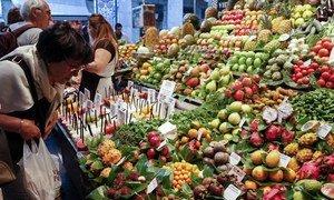 Une consommatrice en train de choisir des fruits sur un marché à Barcelone, en Espagne. Photo : FAO / Alessia Pierdomenico
