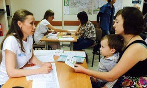 A mother and son receiving a WFP food voucher, distributed by NGO partner, ADRA, in Sloviansk, Ukraine.
