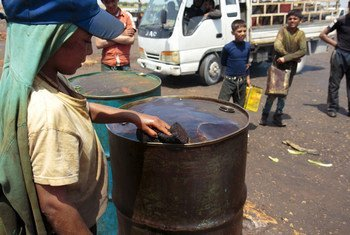 A boy in northern Syria uses a sponge to collect spilled fuel from an oil drum.