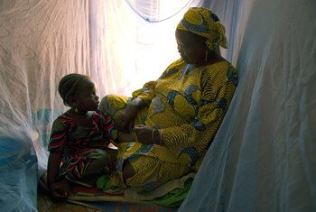 A family in Nigeria utilizes protective malaria bed nets.