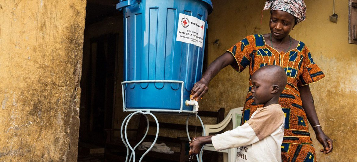 A team of contact tracers is visiting a community in Conakry, Guinea, after a family member was infected with Ebola. The family has been provided with buckets and chlorine and taught how to wash hands properly at home (January 2015).
