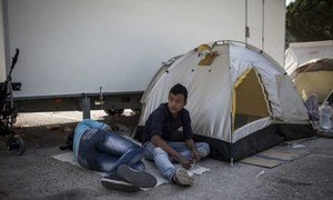 Two boys rest next to their tent outside the screening centre at Moria. Refugees and migrants live in tents until there is space available to accommodate them inside the centre.