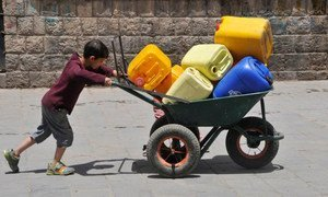 A boy pushes a wheelbarrow filled with jerrycans in Sanaa, the Yemeni, capital.