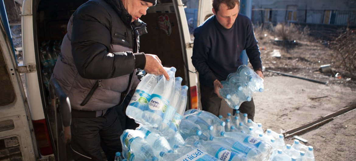 In February 2015, volunteers unload a supply of bottled water, provided by UNICEF, from a vehicle in the city of Debaltsevo in Donetsk Oblast, Ukraine.