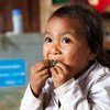 Through a national school feeding program in Oudomxay province, Lao PDR, students get at least a third of their daily energy and nutrition needs. Seen here, a student enjoys her vegetables.