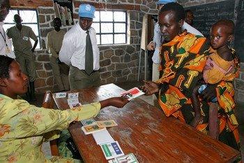 联合国选举观察团的观察员监测布隆迪大选。一名布隆迪妇女领取选举卡。联合国图片/Martine Perret
