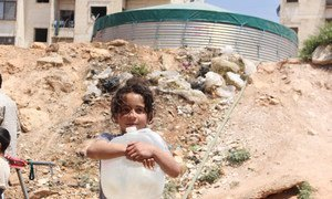 A young girl carries a jerrycan she just filled at a water tank in the Tishreen camp for displaced people in Aleppo, Syria.