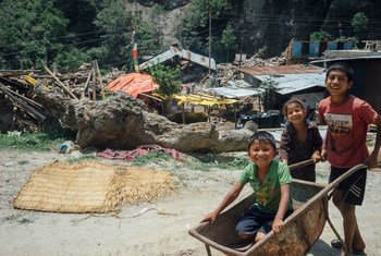 Three children play with a rusted wheelbarrow in the town of Singati, near the town of Charikot in Dolakha District, Nepal, epicentre of the 12 May earthquake.