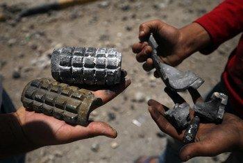 Des enfants tiennent des éclats d'artillerie dans une rue endommagée par des explosions à Sanaa, la capitale du Yémen. Photo : UNICEF / Mohamed Hamoud