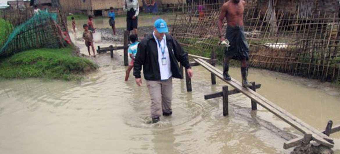 In Myanmar, a UNHCR staff member wades through a flooded section of Nget Chaung camp for internally displaced persons (IDPs) in Pauktaw township, Rakhine State, to assess the damage and identify needs caused by Cyclone Komen.