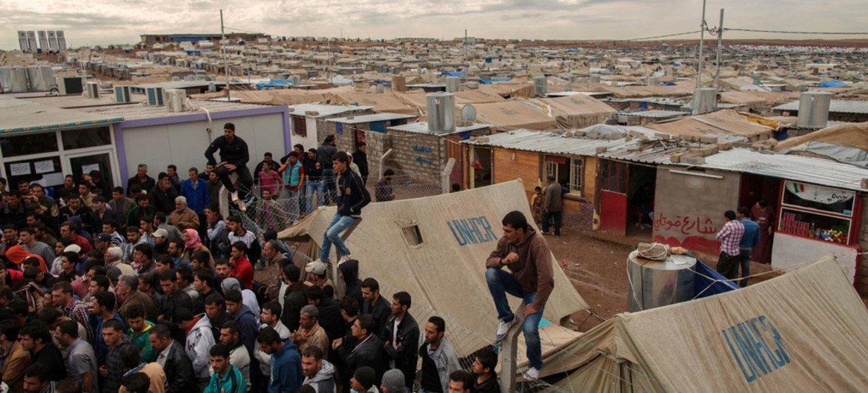 Syrian refugees crowd around an office in Domiz refugee camp in the Kurdistan Region of Iraq.