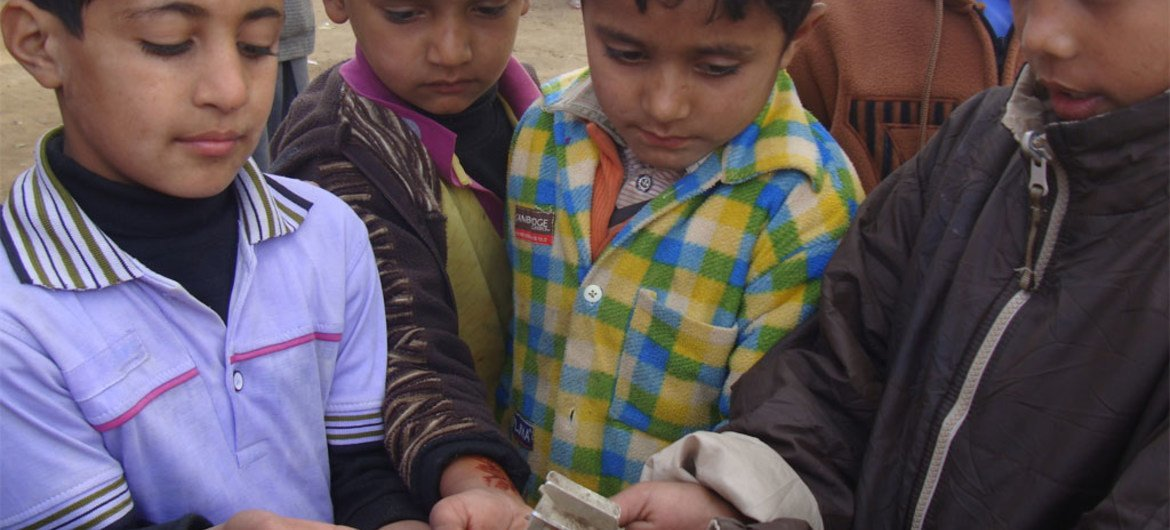Pakistani children hold the remains of a shell that fell during clashes with India in Kashmir.