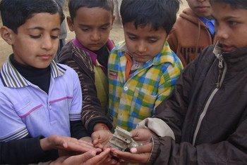 巴基斯坦儿童手持印巴在克什米尔冲突冲遗留的弹片。图片来源:Sumaira Jajja/区域综合信息网资料