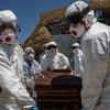 Des opérateurs locaux spécialisés transportent le cercueil d'un migrant mort noyé au large des côtes libyennes (archive)