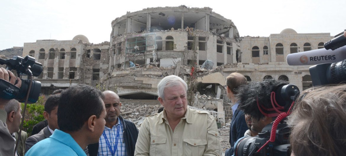 Under-Secretary-General for Coordination of Humanitarian Affairs, Stephen O'Brien (centre) with local authorities and media on 9 August 2015 in front of the Governorate of Amran, Yemen, that got destroyed in an airstrike.