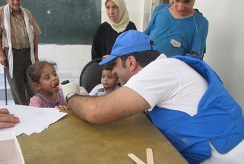 UNRWA doctor examines a child in Yalda, Damascus, Syria, on 19 August 2015.