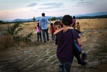 Un jeune Syrien porte son frère à travers la frontière entre la Grèce et l'ancienne République yougoslave de Macédoine, près d'Eidomeni, en Grèce, en juin 2015.  Photo : UNHCR/A. McConnell