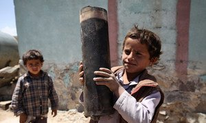 A boy holds a large piece of exploded artillery shell, which landed in the village of Al Mahjar, a suburb of Sana'a, the capital of Yemen.