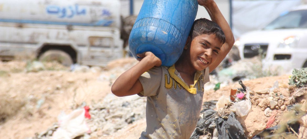 In the Tishreen camp for displaced persons in Aleppo, Syria, a boy carries a jerrycan he filled at a water tank built by OXFAM with UNICEF support.