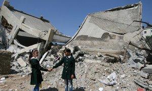 Des camarades de classe se tiennent par la main à côté des décombres d'une partie détruite de l'école des filles Shuje'iyah dans l'est de la ville de Gaza. Photo : UNICEF / Eyad El Baba