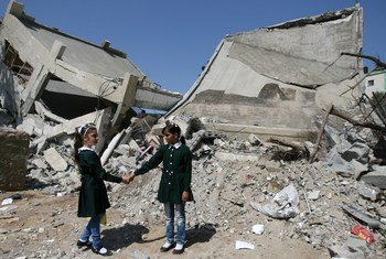 Classmates hold hands while standing beside rubble from a destroyed part of the Shuje'iyah Girls' School in eastern Gaza City.