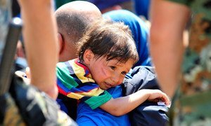On 26 August 2015, a distressed child rests over the shoulder of the man carrying him, in the town of Gevgelija, on the border with Greece and the former Yugoslav Republic of Macedonia.