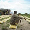 Homem descansa em um saco de arroz distribuído pela Qatar Charity para deslocados internos afetados por enchentes e conflitos em Jowhar, na Somália.