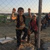 Children stand near the reception centre close to the town of Gevgelija, in the former Yugoslav Republic of Macedonia on 4 September 2015, after crossing the border from Greece together with their families.