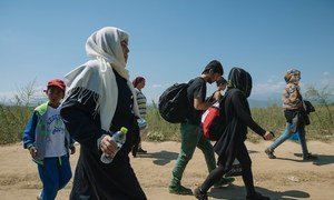 A group of people walking on a dirt road near the town of Gevgelija in the former Yugoslav Republic of Macedonia, after crossing the border at Idomeni in Greece.